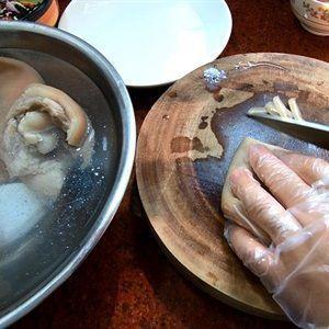 Khi tai heo đã luộc chín, vớt tai heo ra ngâm vào thau nước đá