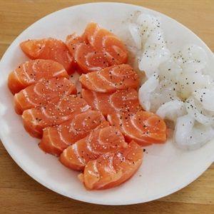 Cá hồi cắt lát, tôm bóc vỏ, rắc muối và tiêu lên cá hồi và tôm